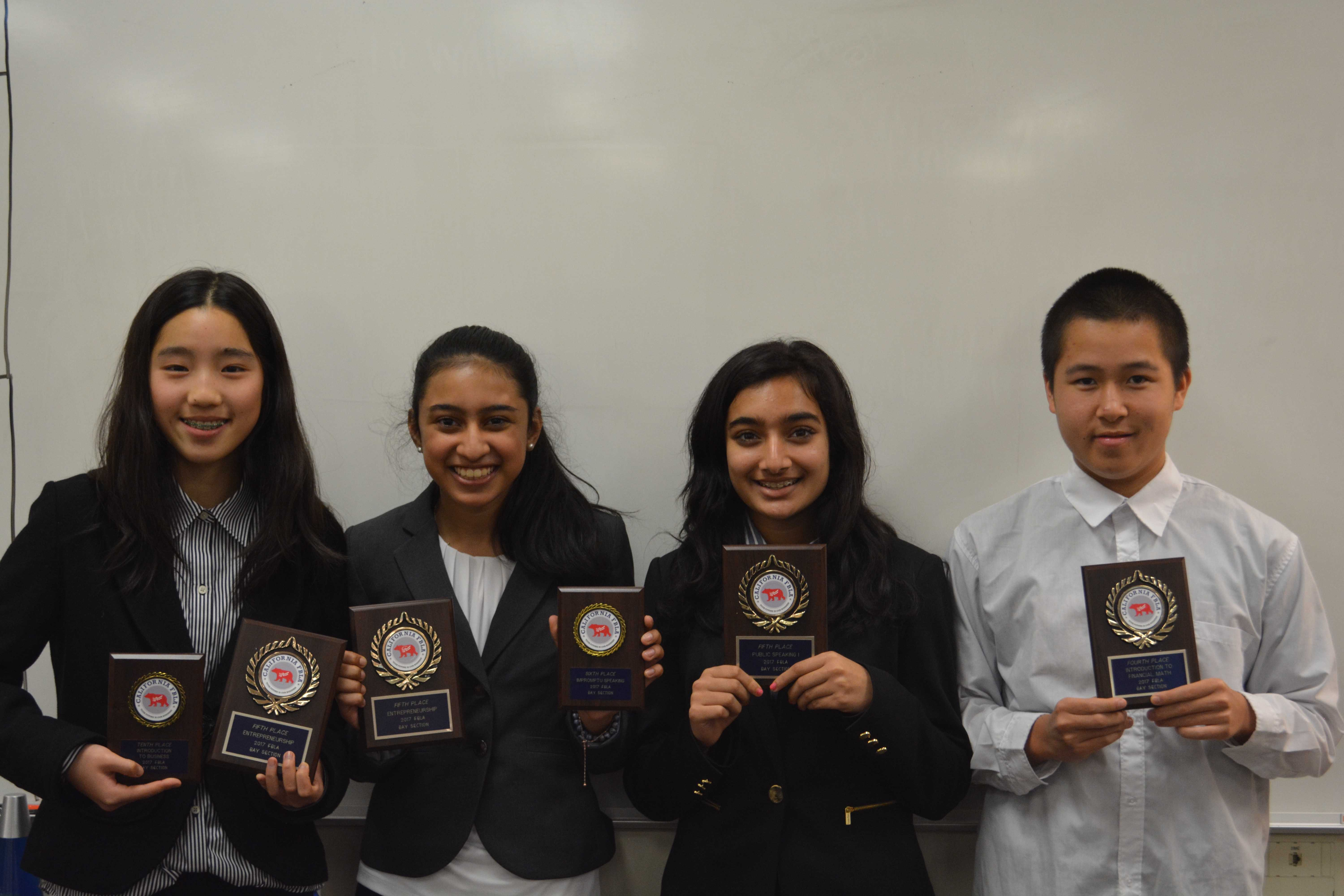 Left to right: Emily Wang, Ria Vora, Soumya Jhaveri and Leyton Ho pose with their plaques after placing at different conference events. Caity Berry, not pictured, also placed at the conference. Wang, Vora, and Ho will be competing at an upcoming state conference.
