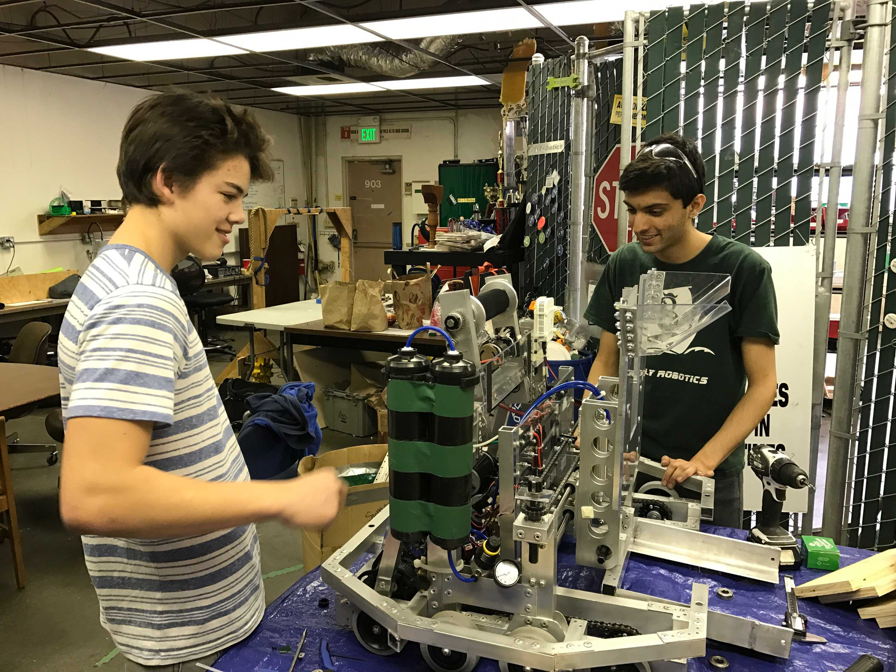 """Sophomore Peter Martin (left) and junior Devin Ardeshna (right) examine the robot in the final hours that they can make modifications. The team hopes to go as far as possible in the upcoming contest. """"In the past couple of competitions we've gone to we've gone to eliminations, so we're hoping to get there again,"""" Ardeshna said. Photo: Jevan Yu"""