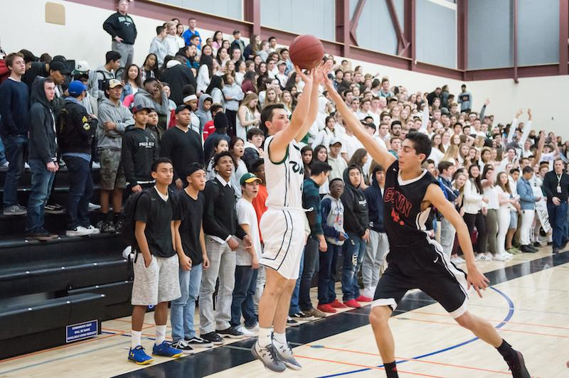 Wulbrun elevates over Gunn High School senior forward David Clarke to knock down a three-point shot during a league match against Gunn. Photo: David Hickey