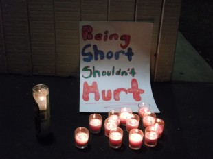 Candles burn around a poster in front of the Tuesday school board meeting.