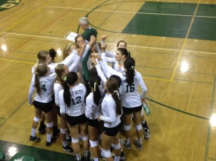 The Palo Alto High School volleyball team huddles together after a fourth set loss.  The Vikings eventually went on to win the match (_)