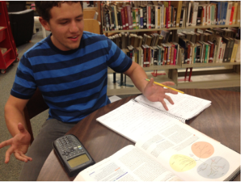 Senior James Ashby discusses his AP Biology homework in the library during his 7th period prep. Photo by Drew Keller.