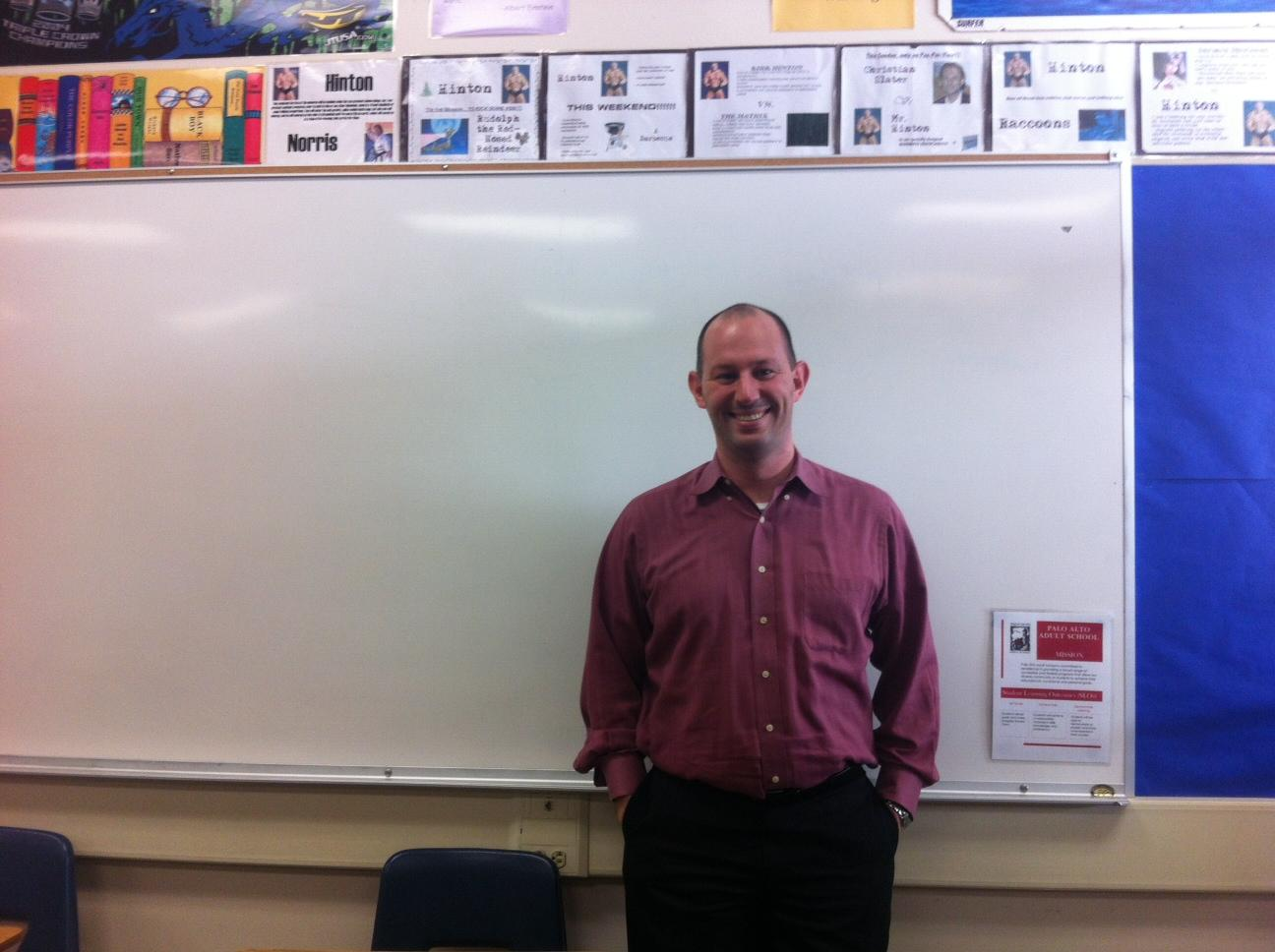 English teacher Kirk Hinton stands at the front of his classroom. Before coming to Paly, Hinton taught in Normandy, France. Photo by Paige Esterly.