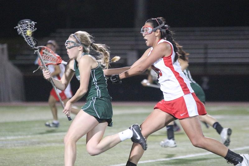 Junior midfielder Allie Peery deflects a blocking attempt by a Gunn defender in the first Gunn-Paly faceoff of this season's league play. Photo by Maddy Jones.