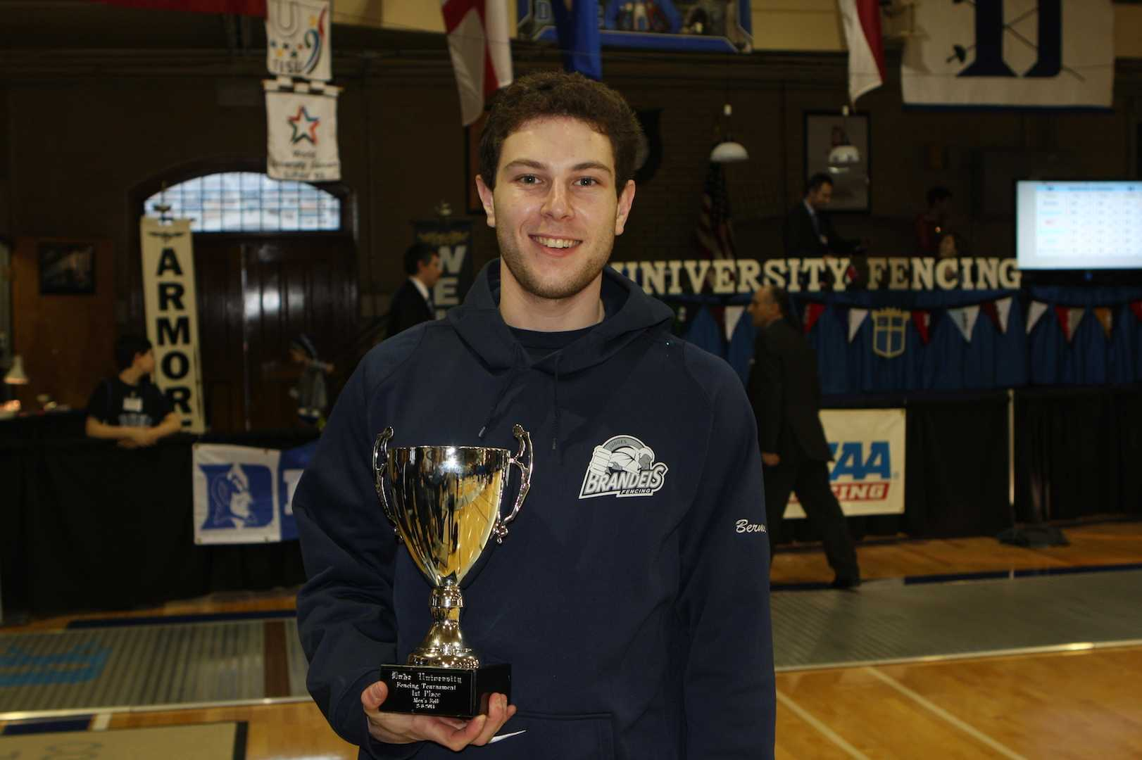 Noah Berman held the tournament trophy he helped Brandeis University win at a fencing meet hosted by Duke University. Photo by Stuart Berman.