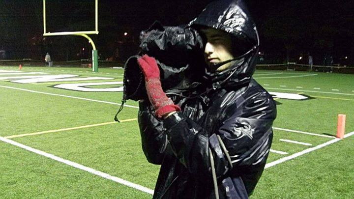 Wes Rapaport films a Paly football game in the rain. Photo by Rebecca Sanders.