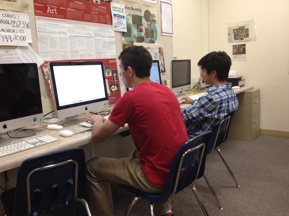 "Sophomore Liam Noroian and junior Edward Chen work in the yearbook's computer lab. Palo Alto High School's yearbook staff plans to distribute the 2013-14 yearbook the week of May 20. ""It's going to be very colorful,"" Editor-in-Chief Sarah Limb, a senior, said. ""There's more autographing space."" Photo by Allison Cowie."