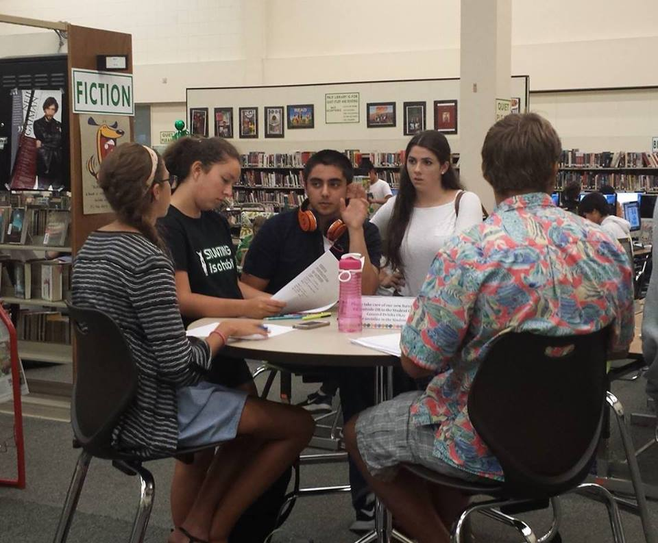 Paly students Olivia Musil, Pasha Kamarei, Lydia Barry and Hans Usman use the café-style high tables in the library. Photo by George Lu.