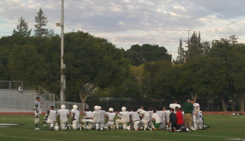 Members of the Palo Alto High School football team take a knee in the middle of the field prior to their August 29 scrimmage against Aragon. Photo by Josh Yuen.