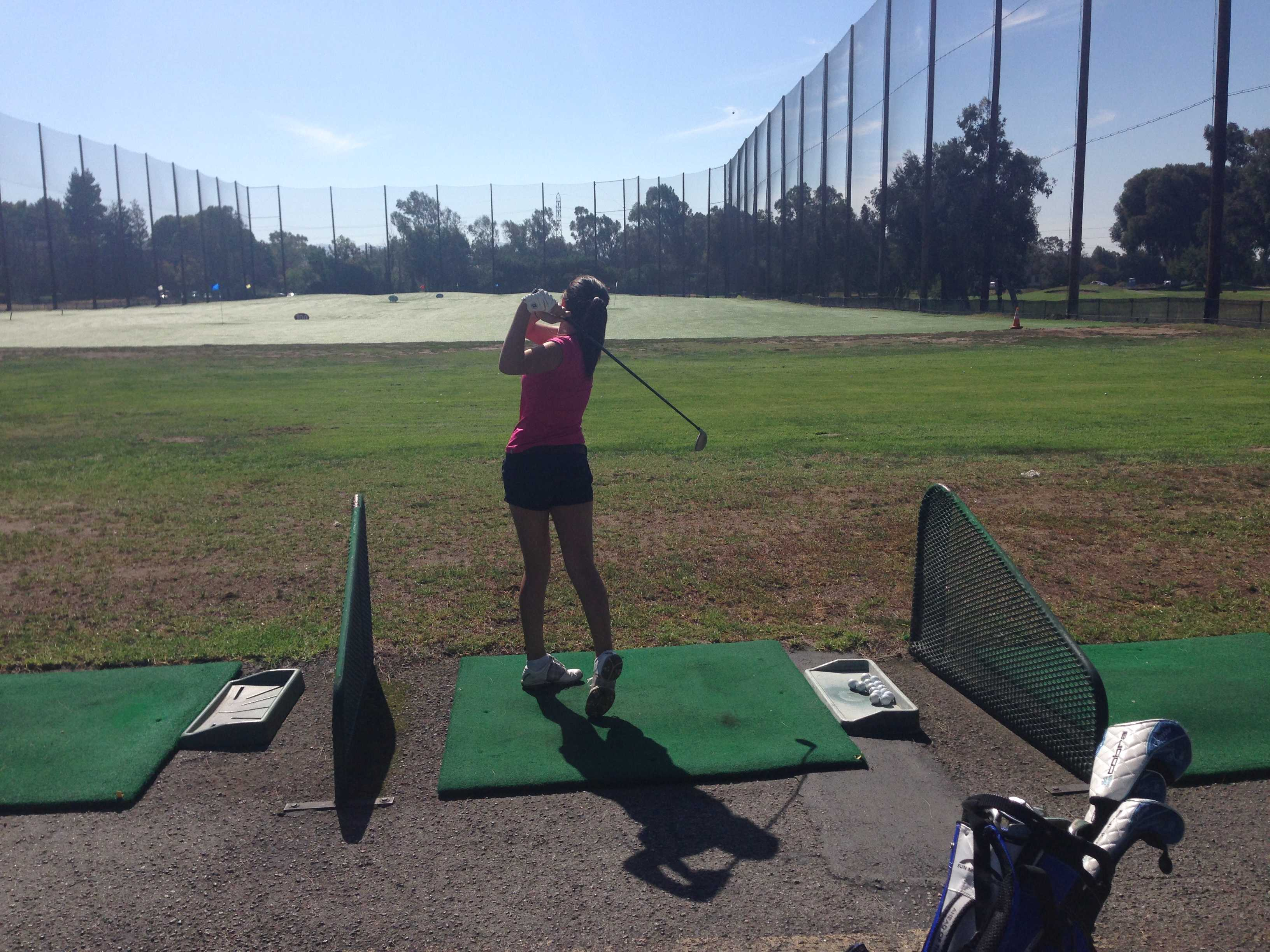 Senior Olivia Johnson takes a swing during practice at the Palo Alto Municipal golf course. Photo by Claire Krugler.