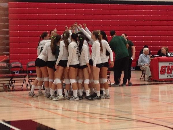 Palo Alto High School girls' volleyball team cheers in their huddle right before their first league game against rival, Gunn High School. Photo by Amy Leung.