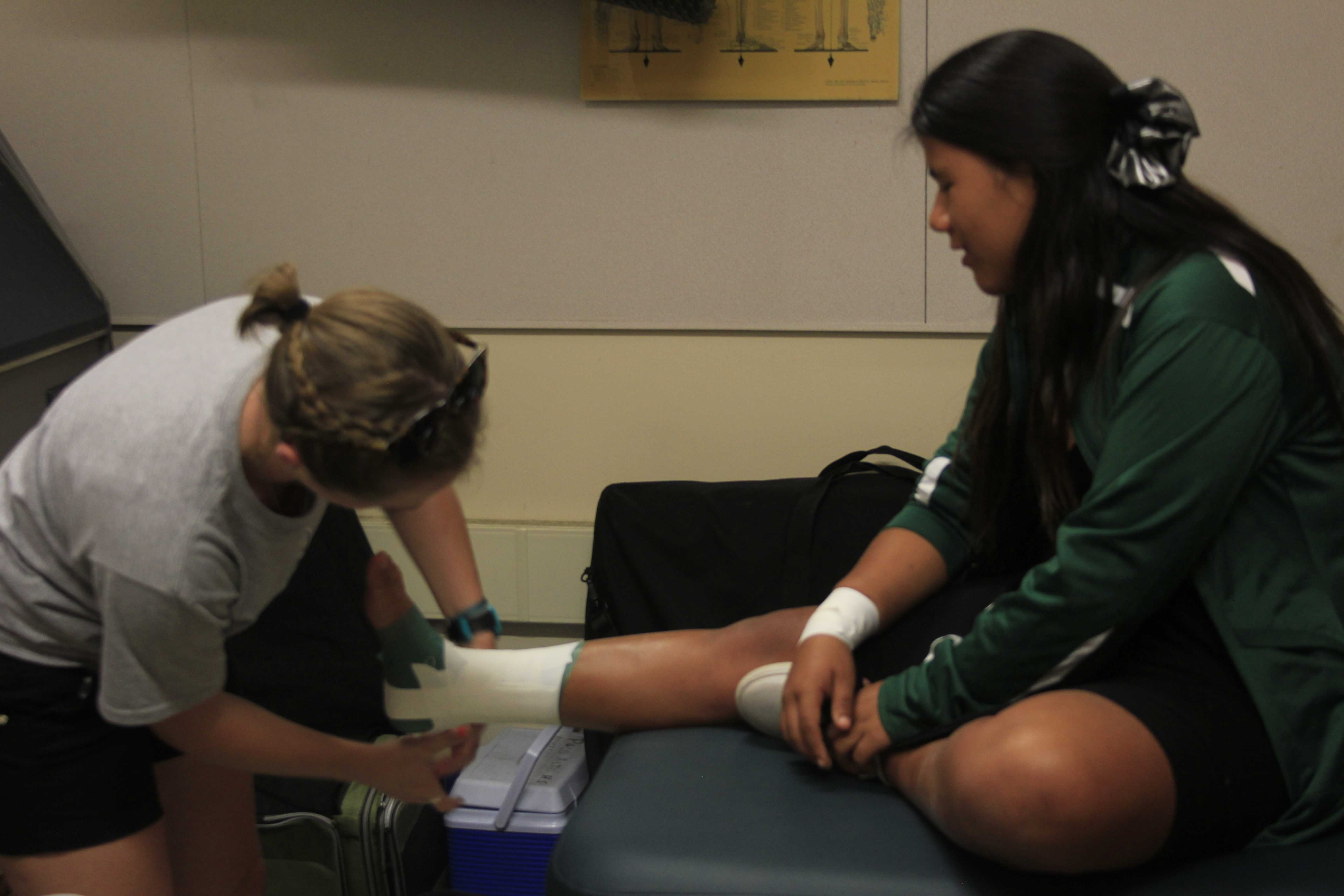 New athletic trainer Kimmy Mathews helps tape freshman Mayerly Short ankle before soccer practice.