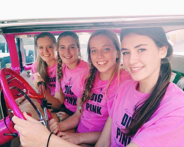 Junior Claire Krugler, sophomore Katie Passarello, senior Molly Fogarty, and alumna Becca Raffel sit in assistant coach Jekara Wilson-Gaines's pink car during last year's Dig Pink event. Dig Pink matches include more decorations and  than normal games. Photo courtesy of Molly Fogarty.