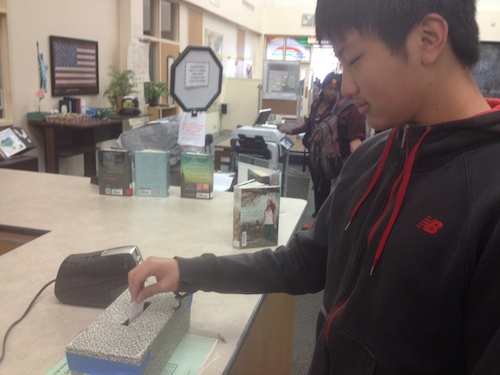 Paly junior Adrian Wang places his comment in the comment box, which is located at the front desk of the library. Photo by Will Zhou.