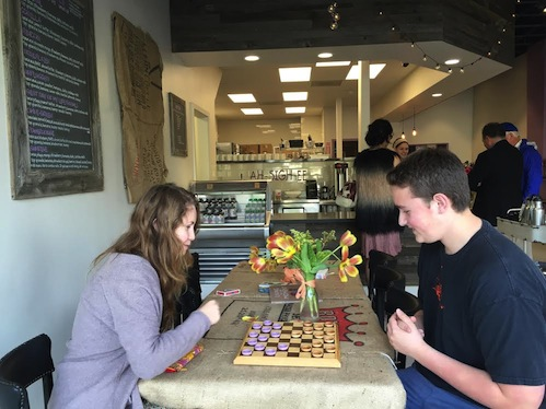 Senior Oskar Soderberg and junior Molly Kraus play checkers at Bare Bowls. Bare Bowls focuses on a community feel with open spaces and communal tables and games. Photo by Alex Merkle-Raymond