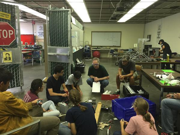 """Paly robotics team listens to an instructor on how to complete the task. The robotics team is currently going through unofficial """"try-outs"""" to see who can remain on the over-full team. Photo by Freddy Kellison-Linn"""