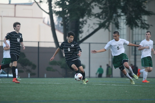 Schoenberger rushes up to Gunn senior forward Sean MacPherson to try to reach the ball. Paly defeated Gunn 3-0. Photo by Amy Leung.