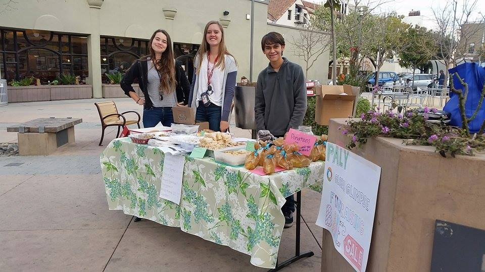 From left: Juniors Rebecca Sunnerås Jonsson, Claire Krugler and Eli Craveiro Frankel, all participants in the Global Glimpse program, set up a bake sale in downtown Palo Alto. Global Glimpse attendees are expected to fundraise in preparation for their trips to Latin American countries. Photo courtesy of Minyoung Kim.