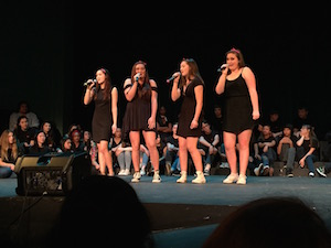 Seniors Jamie Garcia, Claire Chevallier and Casey Glassford sing with sophomore Katie Hetterly at the Pops Concert. The Heartbeats have won awards at the past two small ensemble concerts. Photo by Alex Merkle-Raymond.