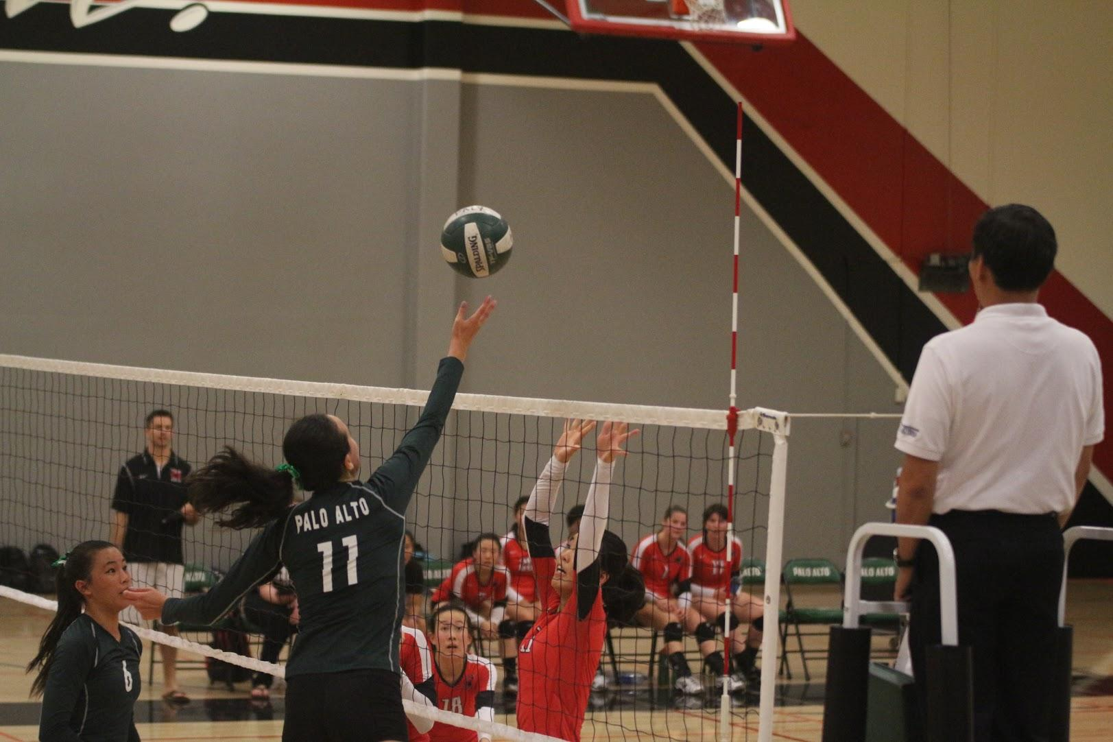 Senior middle blocker Claire Dennis tips the ball over the net. According to head coach Jekara Wilson, Dennis played outstandingly on Thursday against Paly's cross-town rivals, the Gunn Titans.