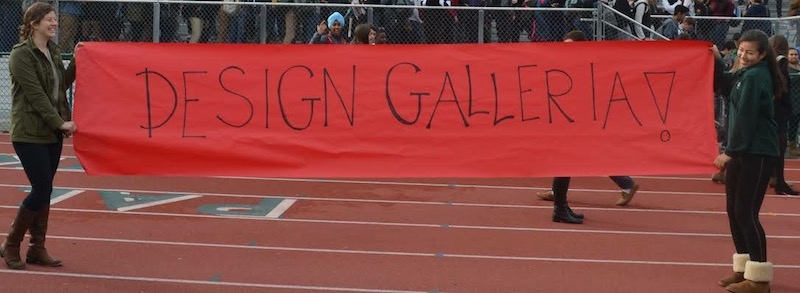 ASB members Cezzane Lane (left) and Natalie Maloney (right) display a banner stating 'Design Galleria'. The prom location announcement was made during the Winter Rally earlier today.