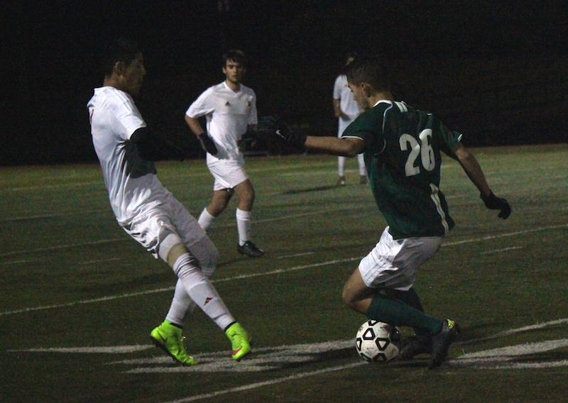 Junior midfielder Jack Stoksik overcomes his defender. Stoksik provided two of the critical passes that led to the first two goals of the game against Palo Alto High School's cross-town rivals, the Gunn Titans.