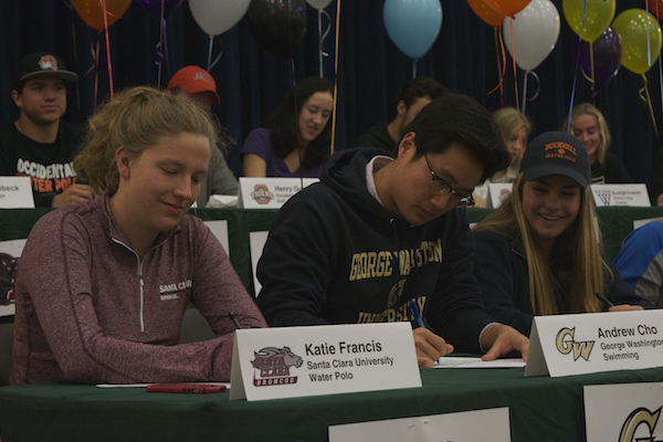 Seniors Katie Francis and Andrew Cho sign their college athletic letters of intent on Wednesday in the Media Arts Center. Francis will be attending Santa Clara University for water polo and Cho will be attending the George Washington University for swimming.
