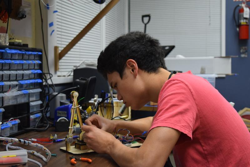 Senior Nathan Kau works on his robotic arm in preparation for the regional tournament this weekend.