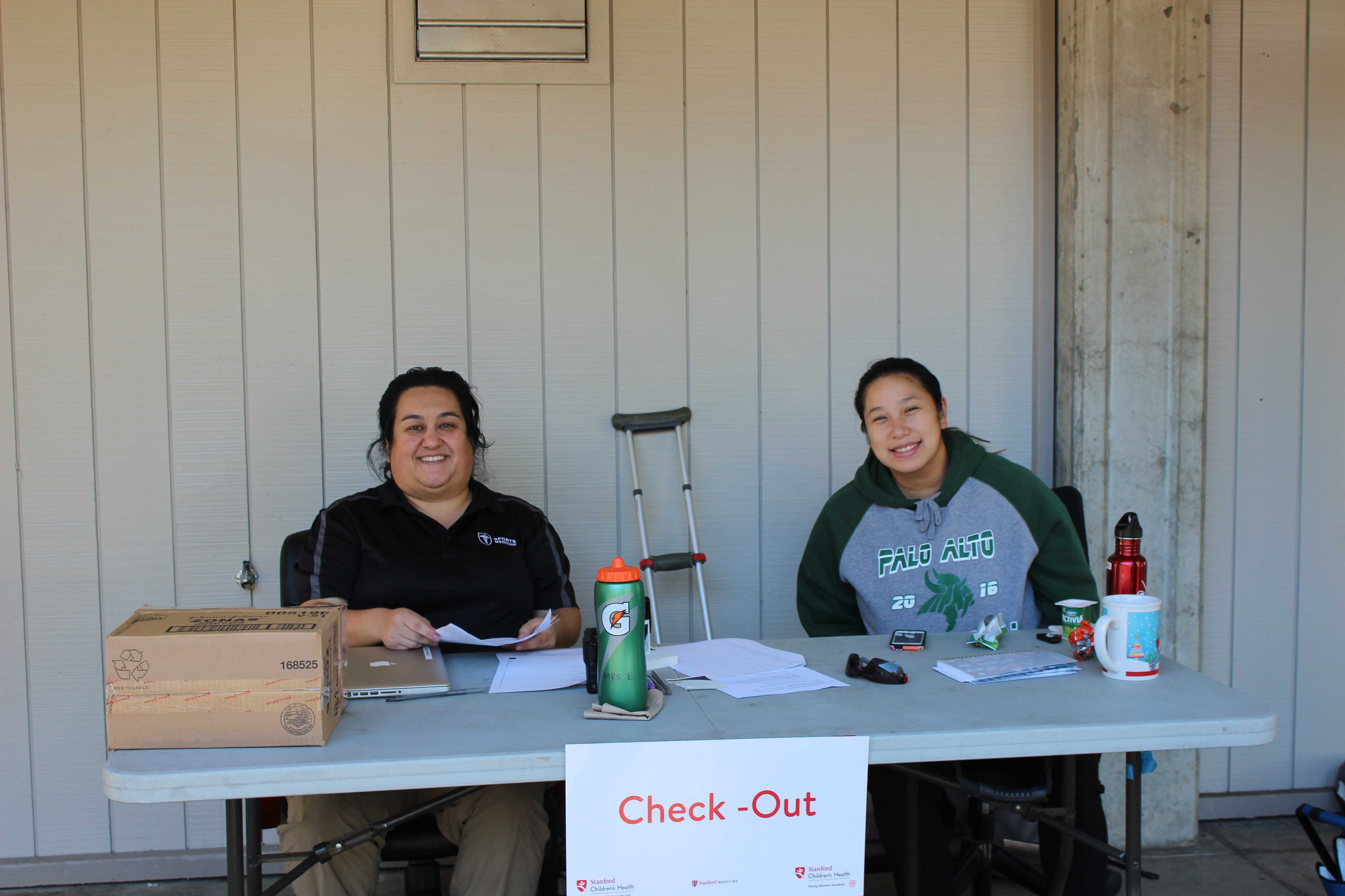 Justine Iogini and a volunteer with the Palo Alto High School athletics department work together with Stanford in providing athletes sports-med services at Gunn High School. Photo by Bianca Al-Shamari.