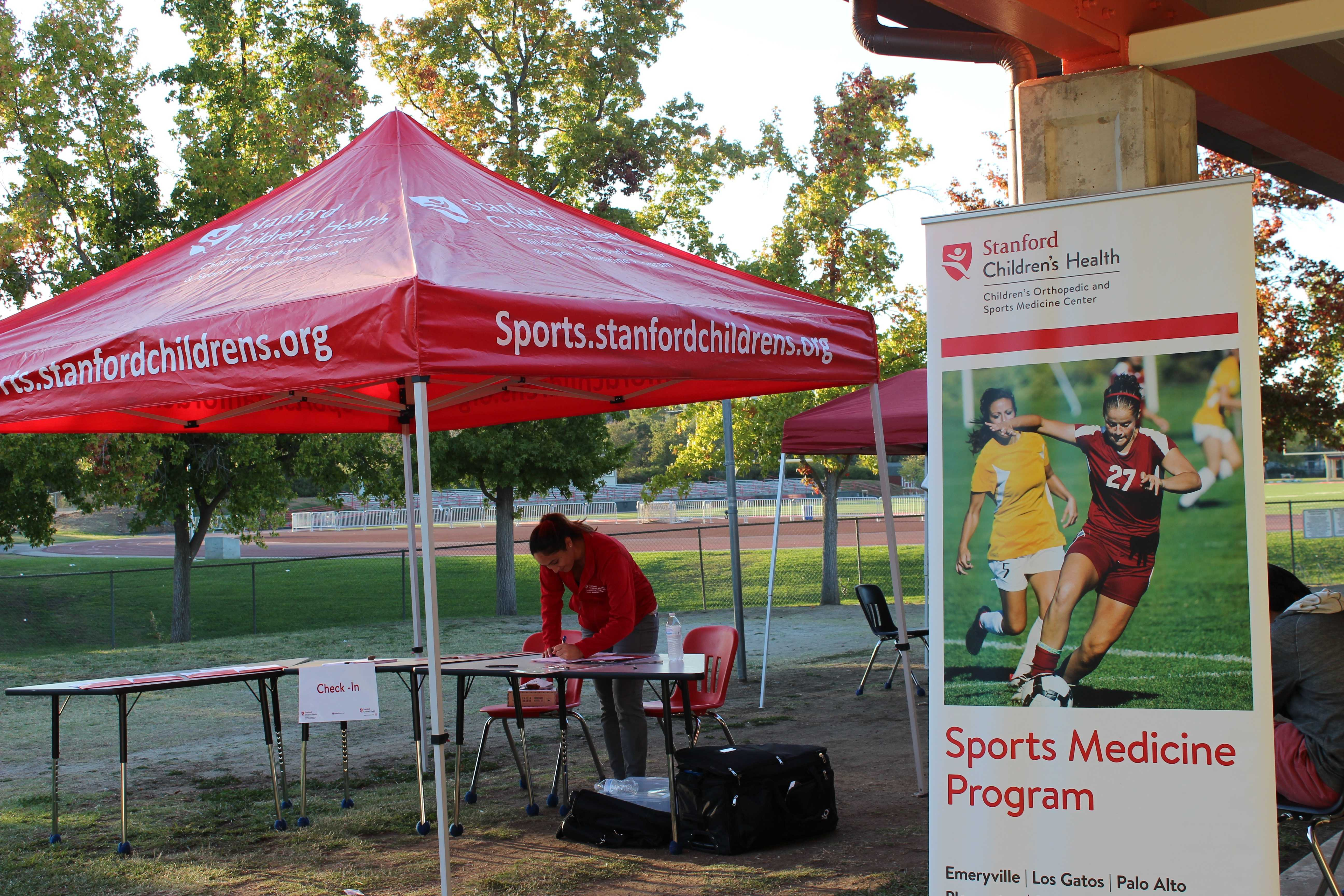 A stanford Athletic Supervisor mans the check-in desk for Palo Alto student athletes receiving their physicals through the Young Athletes Academy program. Photo by Bianca Al-Shamari.