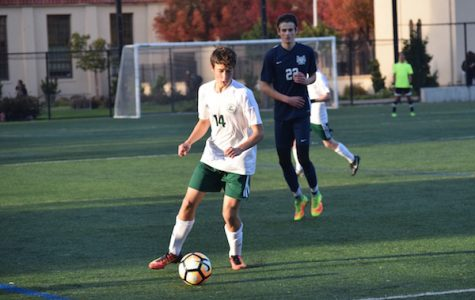 Junior outside midfielder Jason Shorin dribbles up the sideline. Shorin is a second-year Varisty player on the boys' soccer team. Photo: Emma van der Veen.