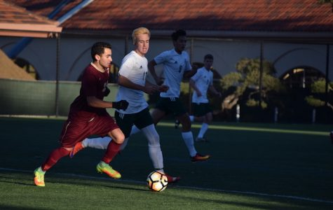 Palo Alto High School senior Charles Stoksik races against a Menlo-Atherton player, trying to keep the ball away from the Viking's goal on Tuesday at Paly. The Palo Alto High School boys' soccer team defended their early lead in a close match, winning the game 1-0. Photo: Annika Behal.