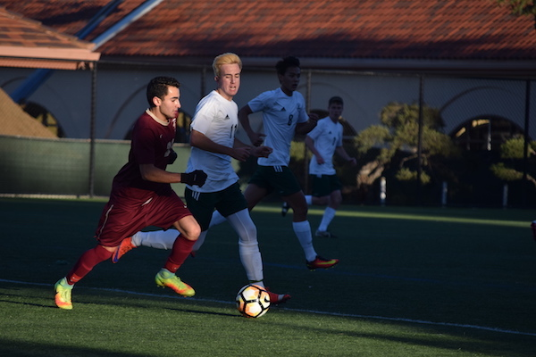 Palo Alto High School senior Charles Stoksik races against a Menlo-Atherton player, trying to keep the ball away from the Vikings goal on Tuesday at Paly. The Palo Alto High School boys soccer team defended their early lead in a close match, winning the game 1-0. Photo: Annika Behal.