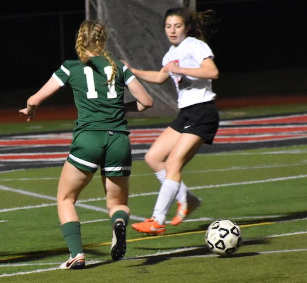Sophomore forward Mia Zenger dribbles past Gunn defenders last Thursday during a preseason match at Gunn. Photo by Rachel Code.