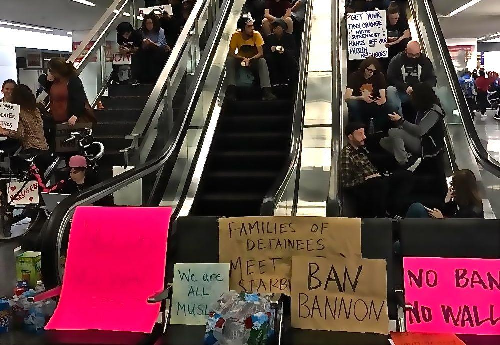 Protesters block escalators in SFO's international terminal. Photo by Lia Straight.