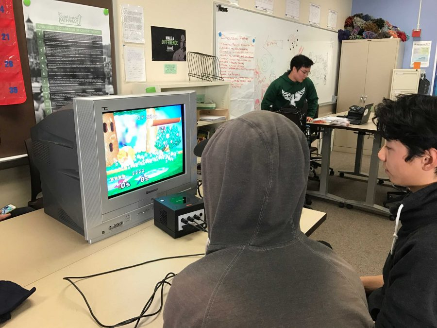 """Sophomore Vice President Anthony Xie, right, and senior Tai Nguyen, middle, battle on Smash melee during a club meeting on Jan. 30. Although Xie won this time, Nguyen is almost always the victor. """"He was going easy on me,"""" Xie says."""