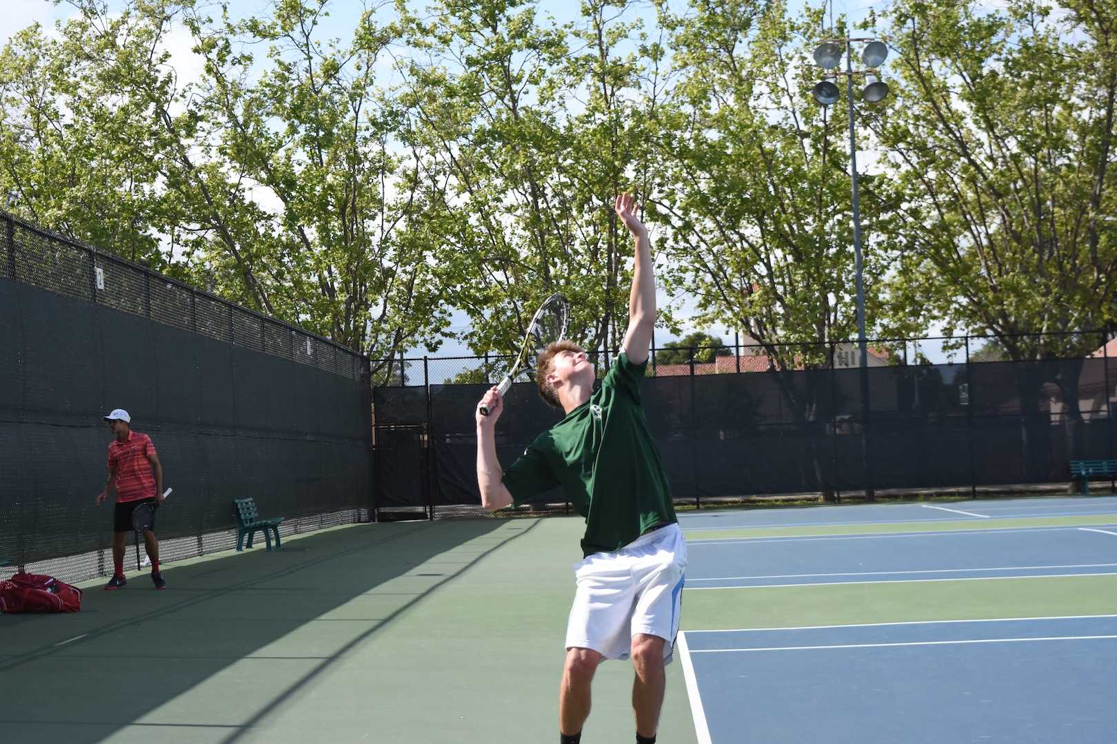 Senior Adrian Tompert serves a ball to his opponent.