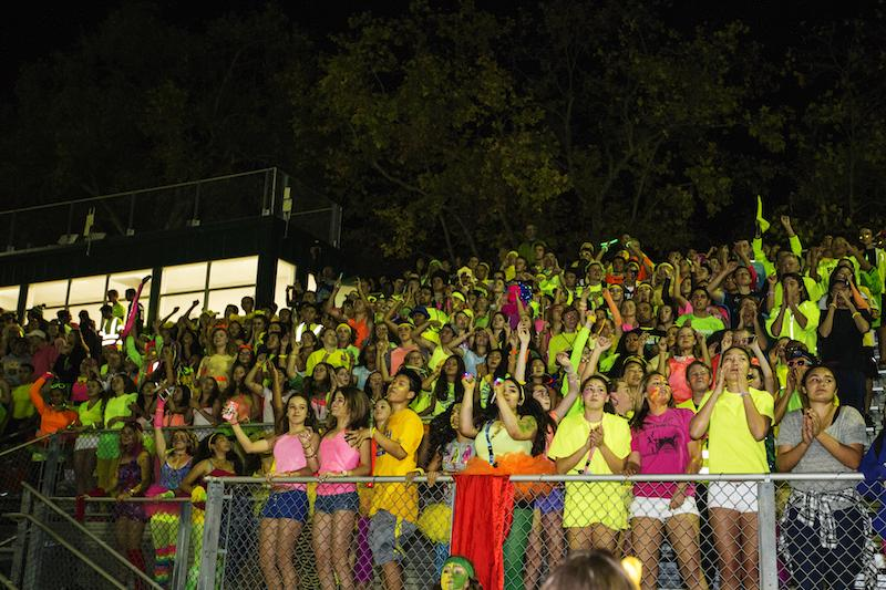Paly students, decked out in neon clothing, cheer for their separate classes during a relay race during the 2015 spirit night rally. Photo by Cooper Lou.