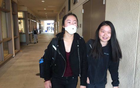 Stephanie Yu wears a mask to prevent breathing in the smoke. Many students wore masks or used their hoodie to cover their mouth and nose. Photo: Samantha McBride
