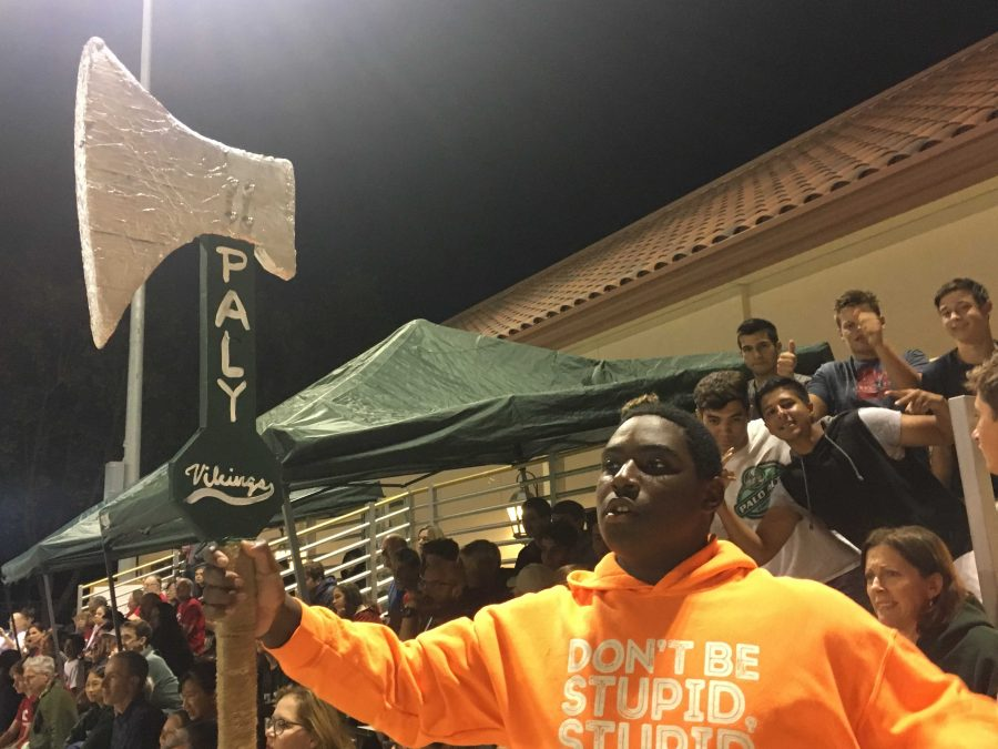 Junior Alex Daw raises an axe to cheer for the team, and other students in the stands support him energetically. Photo: Soumya Jhaveri