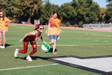 Freshman Miranda Jimenez runs with the beachball to pass it to the next relay station. Photo Credit: Angelina Wang