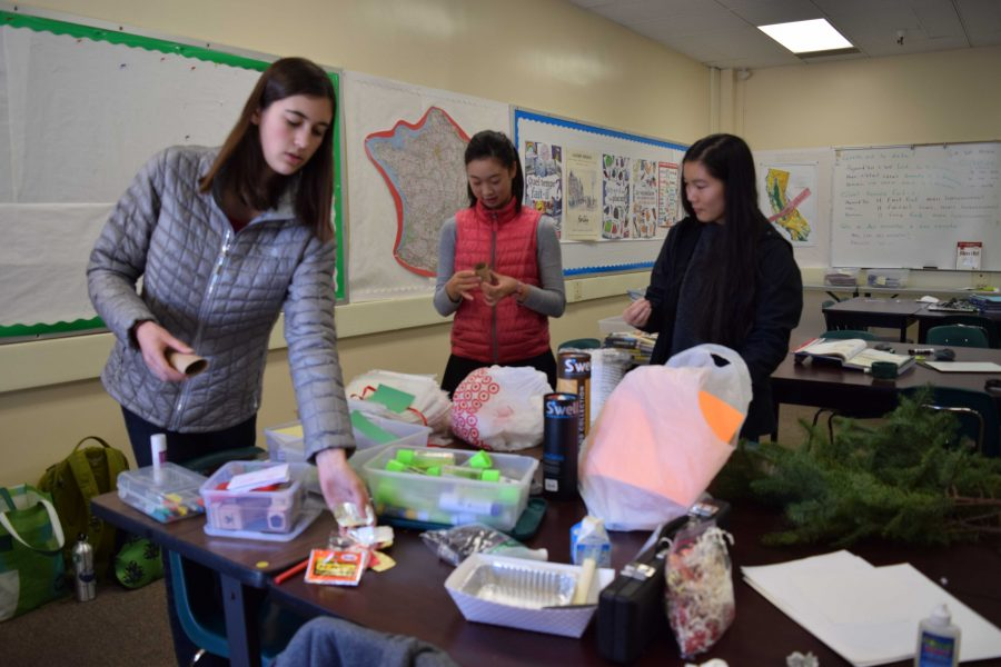 Members of Zero Waste Initiative Club prepare for tomorrow's Tap Out Tuesday event. Their booth allows students to make holiday decorations out of old recyclables which they can take with them.