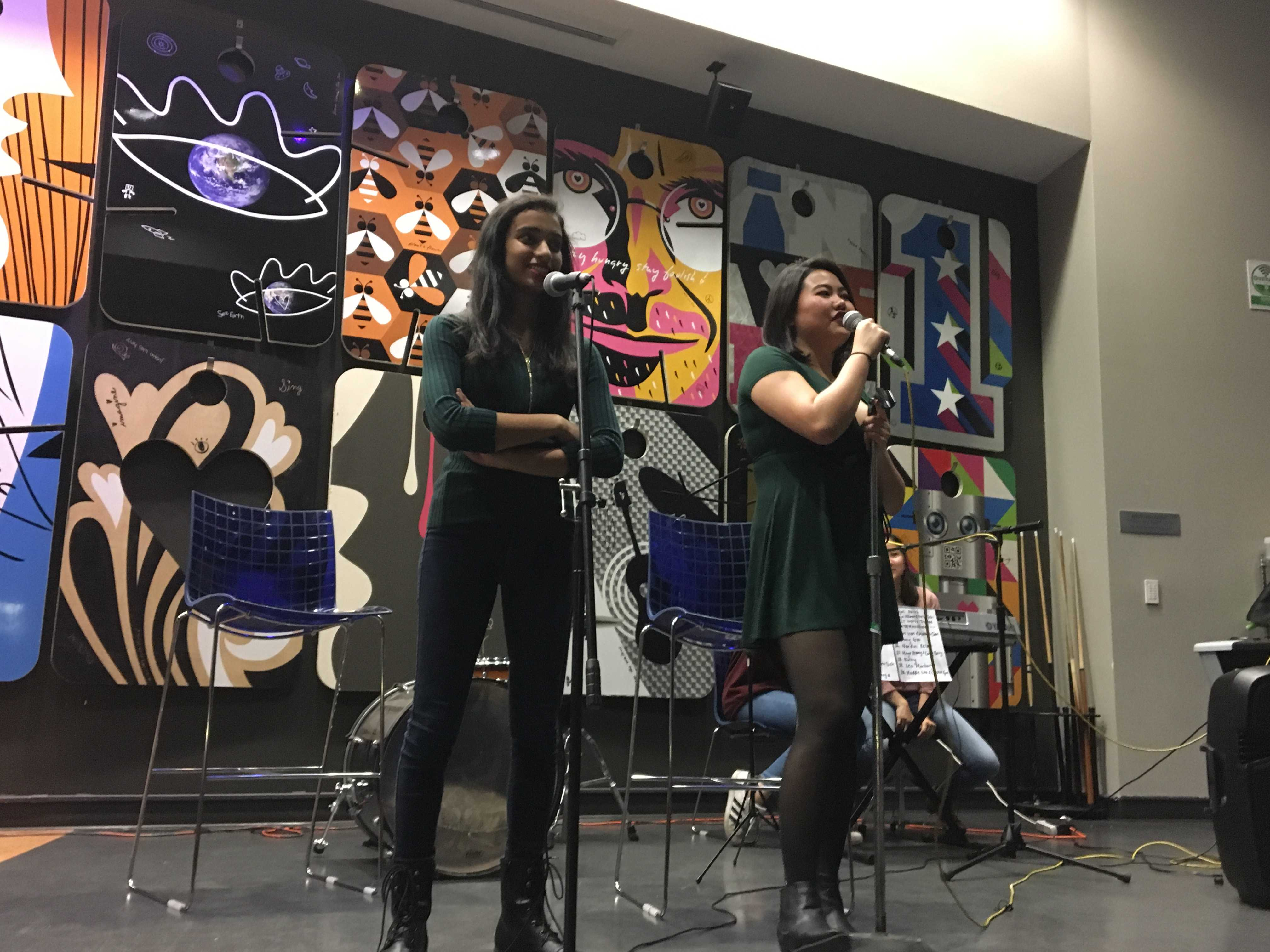 "TAC President Nandini Relan and Publicity Officer Emily Zhang (left to right) introduce the next performer. ""The best part [of open mics] I have to say is just the atmosphere and getting to see such a variety of performers and performances."" Photo: Maya Akkaraju"