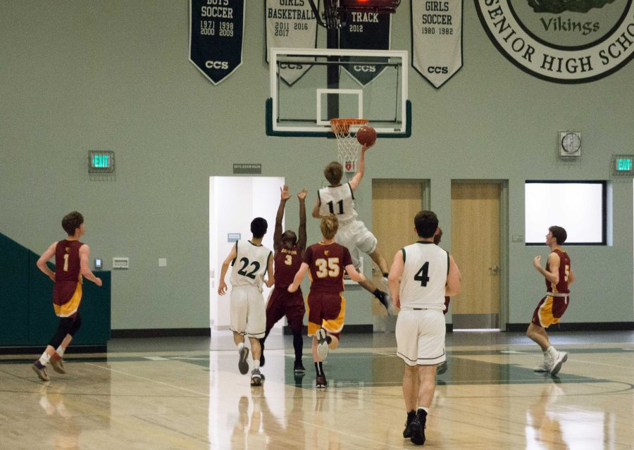 Senior forward Max Dorward, who led Paly with 17 points, shoots a layup over a defending Menlo-Atherton player. The Vikings played stout defense all night and attacked the paint on offense, resulting in a 57-41 win at the Peery Family Center.