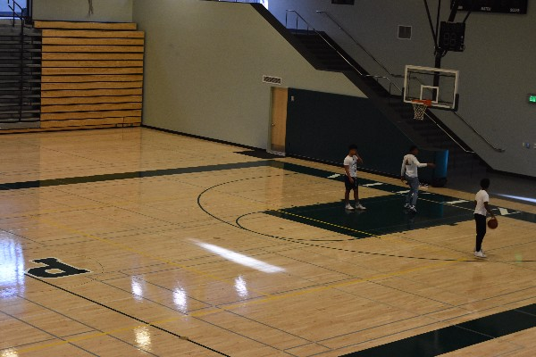 "Sophomores Junacio Henley and Jamir Shepard, Junior Dwayne Trahan shoot hoops in the Peery Center's Large Gym. The Associated Student Body will hold the Winter Rally basketball game between students and staff in the Large Gym on Jan. 23. ""We hope to have a huge turnout because this is a really fun event and a cool Paly tradition,"" Junior Site Council Representative Riya Kumar said."