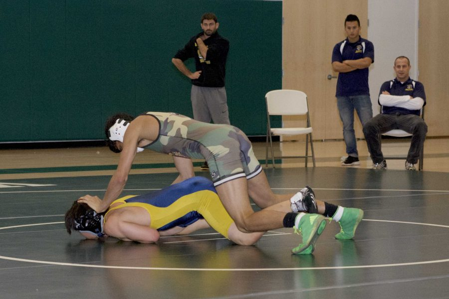 Palo Alto High School varsity wrestler Calvin Grewal takes down his opponent, winning by technical fall. The dual meet against Milpitas High School marked the first time the Vikings competed in the new Peery Family Center.