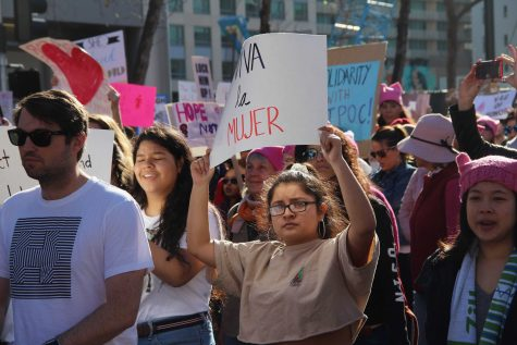 "A young woman holds up her sign, which reads ""viva la mujer"", or ""long live the woman"", as she marches. Many marches  had signs in spanish, and signs that supported immigrants"