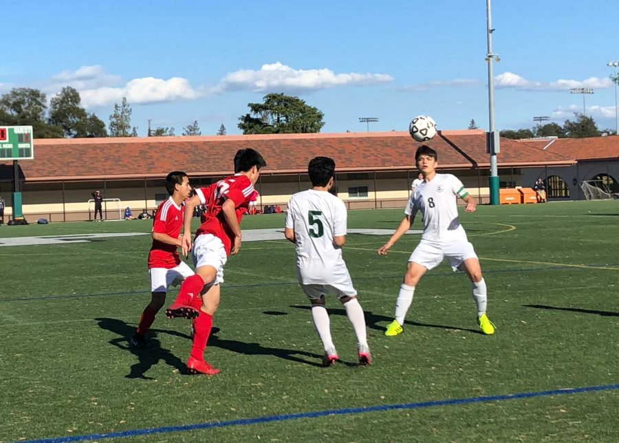 Senior captain center midfielder Xander Scherer heads the ball in an exciting match against rival Gunn High School (12-7-1, 9-3-0) on Wednesday at the Viking lacrosse field. This match resulted in a 2-0 win for Palo Alto High School.