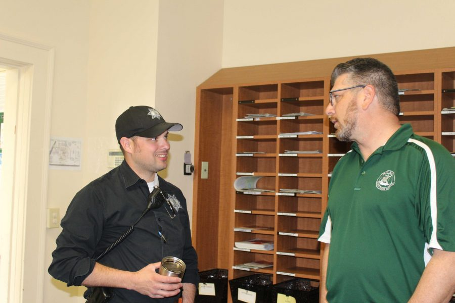 Assistant Principal Jerry Berkson speaks with one of the patrolling officers in the main office. Following the lockdown, the Paly administration and the Palo  Alto Police Department are working together to find the person that made the threatening phone call to Paly.
