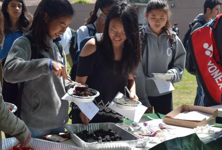 "Sophomore Samantha Pao, left, grabs a healthy snack on the Palo Alto High School Quad quad. Parent volunteers served locally grown fruit and granola during Day 1 of Change in Our Schools Week, which focuses on stigmatized issues that need more awareness at Paly. ""Change in Our Schools Week is something that the School Wellness and Climate Committee has been working on that is basically a whole week long full of events during lunch time that focus on changes in our school,"" junior Noor Navaid said."